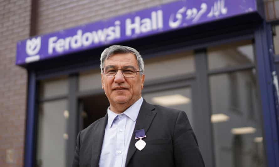 Dr Nooralhaq Nasimi, the founder of the Afghan and Central Asian Association (ACAA), standing outside a sign reading Ferdowsi Hall.
