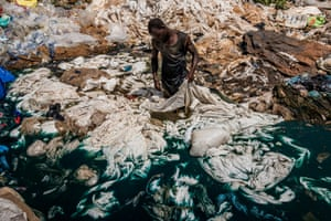 A man rinses plastic bags in a rubbish dump in marshland, where the blue dye from the plastic runs into a lake in Uganda. The wetlands form a natural filter for surface water, but poor people in search of work settle there, causing pollution and damage to the environment