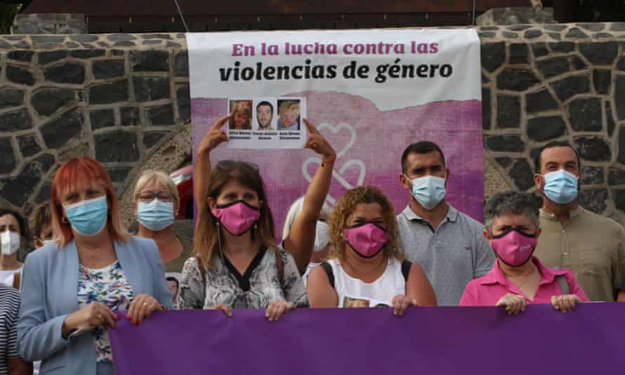 Anti-gender-based violence campaigners hold up a picture of two girls and their father