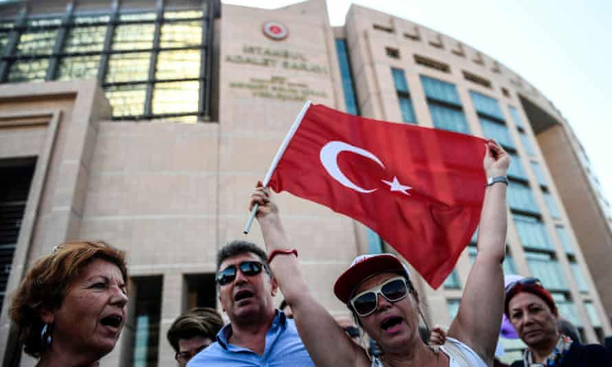Demonstrators outside Istanbul's courthouse, where 17 journalists are on trial.