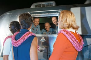 The crew, looking through the window of a mobile quarantine facility, arrives on 27 July 1969 at Houston's Ellington air force base, where they were welcomed by their wives, left to right, Pat Collins, Jan Armstrong and  Joan Aldrin