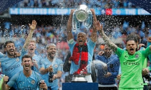 Manchester City's Vincent Kompany lifts the trophy as his teammates celebrate their victory.