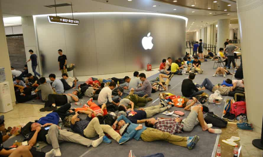 People queue outside the Apple store in Nanjing before its opening on Saturday.