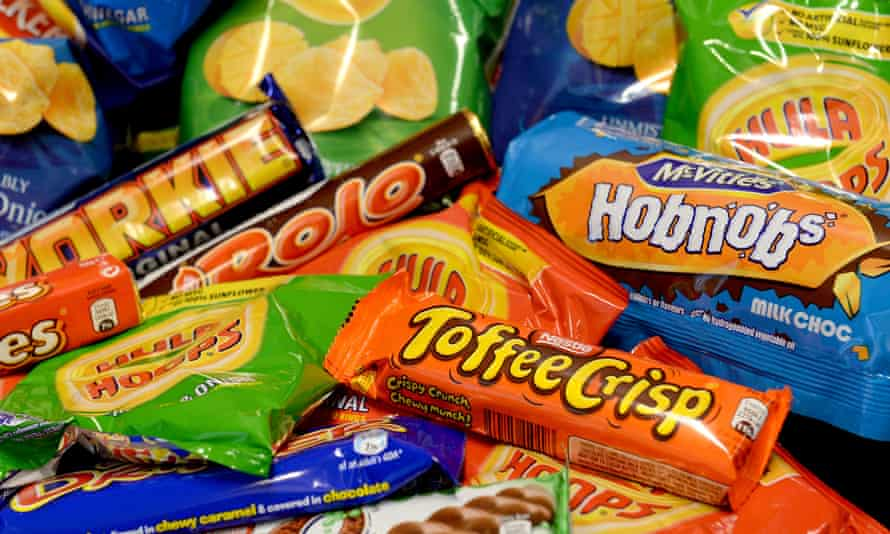 collection of biscuits, crisps, chocolate bars and carbonated drinks. A study by British universities has found that shoppers at supermarkets which removed sweets and crisps from checkouts purchased almost a fifth less of the unhealthy products. PRESS ASSOCIATION Photo. Issue date: Tuesday December 18, 2018. Researchers found that 17% fewer small packages of sugary confectionery, chocolate and crisps were bought and taken home from supermarkets after they introduced policies to limit unhealthy foods at the tills.