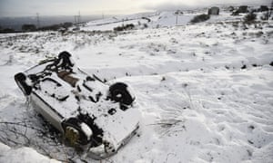 An abandoned car lies in a snow-covered ditch in Belfast, Northern Ireland