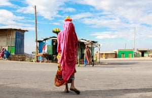 Harar, Ethiopia. Portrait of a woman wearing a vibrant pink dress that covers her head. A woman on her way to market has no idea that she is central to the vibrant rainbow of colours in this city in the east of Ethiopia.