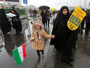 A woman carrying a sign reading 'Down with USA' marches with a girl holding a national flag