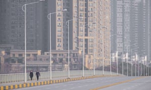 People wearing face masks walk down a deserted street in Wuhan.