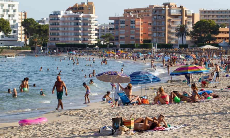 Tourists sunbathe at Palmanova beach in Mallorca in July.