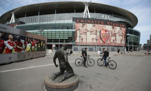 Two cyclists in front of Arsenal's stadium