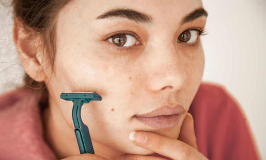 Woman holding a razor to her face