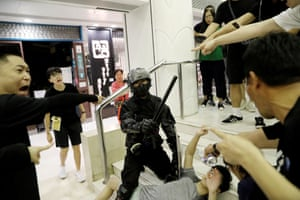 A riot police officer detains a protester at a shopping mall in Tai Po.