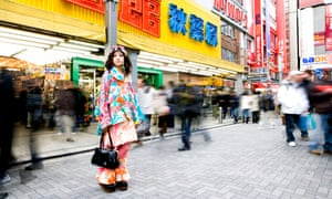 Young woman standing in front of electric department store japan