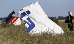 A woman takes a photograph of Malaysia Airlines flight MH17 wreckage