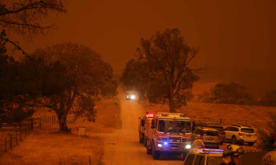 Day turns to night in the town of Adaminaby, New South Wales, as fires approach. Australia has received offers of troops and support from its regional allies, including New Zealand.
