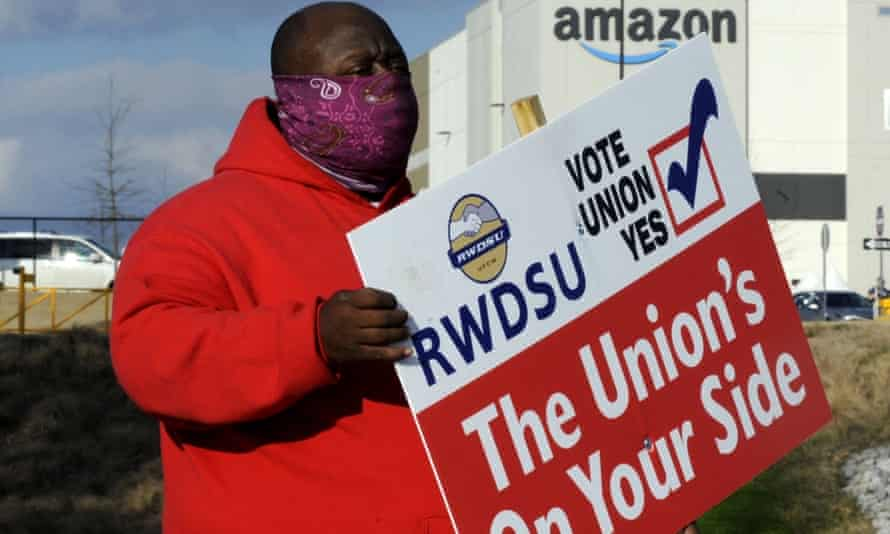 Michael Foster of the Retail, Wholesale and Department Store Union holds a sign outside an Amazon warehouse where the union is trying to organise workers
