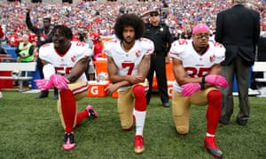 Colin Kaepernick, centre, and his former San Francisco 49ers team-mates Eli Harold and Eric Reid take a knee during the national anthem in 2016.