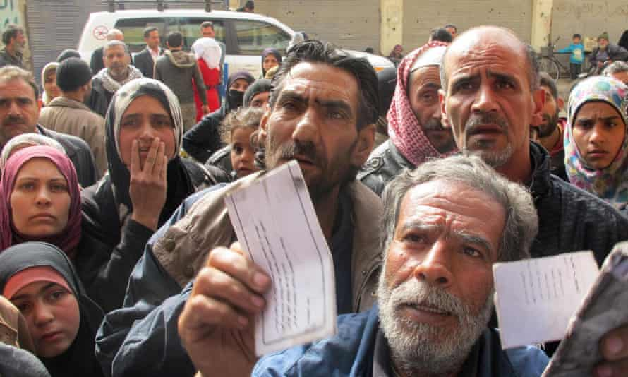 Displaced people from the Yarmouk Palestinian refugee camp queue to receive aid in Yalda, south of Damascus on 16 April 2015.