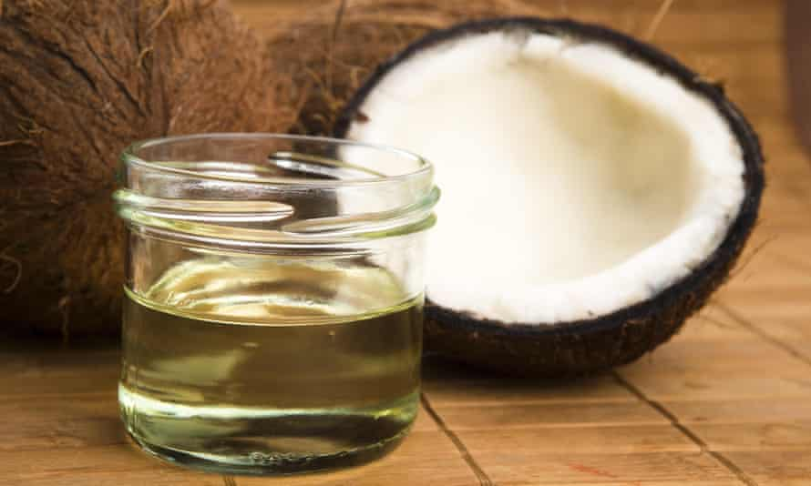 A cracked coconut and a jar of oil