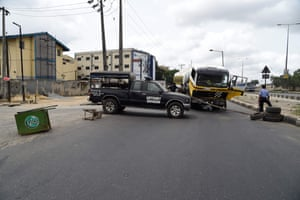 Policemen mount a road block with a stick to prevent the movement of motorists around Lagos on Tuesday