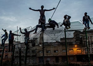 Melilla, Spain, 2014: young Africans cling to the double fence that separates Africa from Europe.