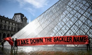 Activists of Pain (Prescription Addiction Intervention Now) holding a banner reading 'take down the Sackler name' in front of the Louvre museum.
