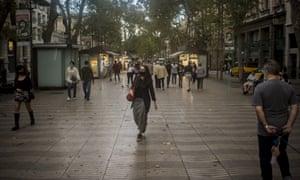 People wearing face masks walk down Las Ramblas boulevard in Barcelona.