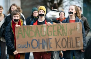Protesters hold a banner reading 'Digging also works without coal' in front of Siemens' headquarters in Munich, Bavaria, Germany. The protest is directed against the possible participation of the German industrial conglomerate Siemens in the Adani coalmine