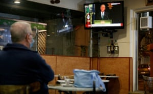 A man watches on a screen in a restaurant as the president declaring the state of emergency, in Cascais, Portugal.