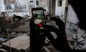 AFP PICTURES OF THE YEAR 2016 A Syrian gamer uses the Pokemon Go application on his mobile to catch a Pokemon amidst the rubble in the besieged rebel-controlled town of Douma, a flashpoint east of the capital Damascus on July 23, 2016. / AFP PHOTO / Sameer Al-DoumySAMEER AL-DOUMY/AFP/Getty Images