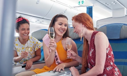 Young women drink champagne on an aeroplane