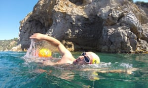 A Vies Braves swimming course around the Costa Brava coastline. Swimmers wear bright yellow caps for extra visibility.