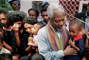 Kofi Annan comforts a crying baby as he meets survivors of the Liquica massacre in East Timor, 1999.