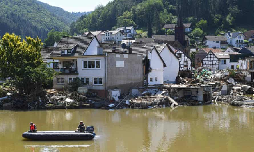 Two military personnel in an inflatable boat travel along a muddy and hugely swollen river past damaged buildings on the riverbank