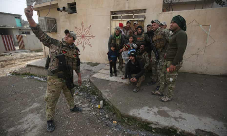 Members of the Iraqi forces pose for a photograph as troops advanced in Mosul's eastern Al-Intisar neighbourhood in 2016.