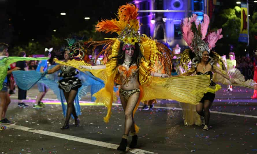 A drag queen in flame orange with a large feathered head-dress and a pleated chiffon cloak that looks like wings ruffles her costume in front of a group of other dancers, in similar outfits, in the middle of the road at night during Mardi Gras.