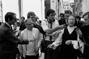 De Beauvoir and Sarte on a Paris street after their release from police custody. They were arrested for selling a newspaper advocating the overthrow of the French government.
