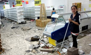 Workers clean the floor next to empty shelves and refrigerators in a supermarket after it was looted in San Cristobal.