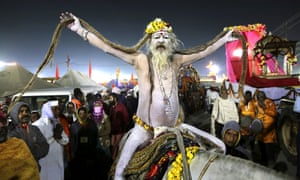 A naked Hindu holy man arrives on a horse back for ritualistic dip on auspicious Makar Sankranti day during the Kumbh Mela