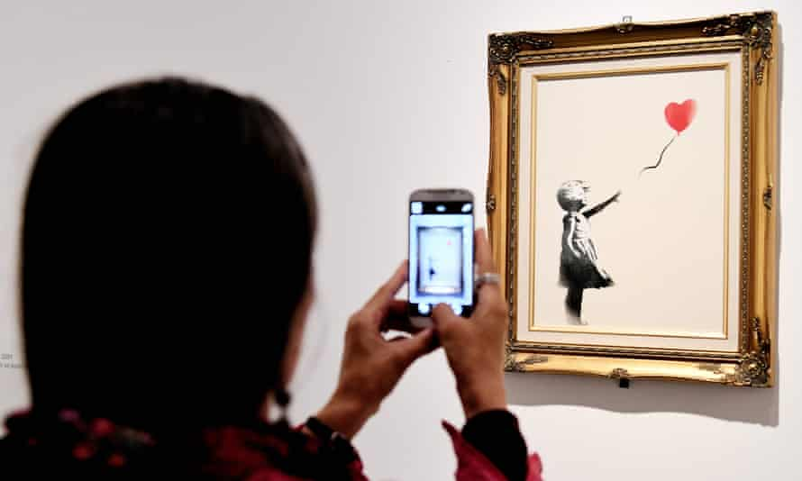"""A woman takes picture on May 23, 2016, of a piece entitled """"Girl with ballon, red"""" by England-based graffiti artist Banksy"""