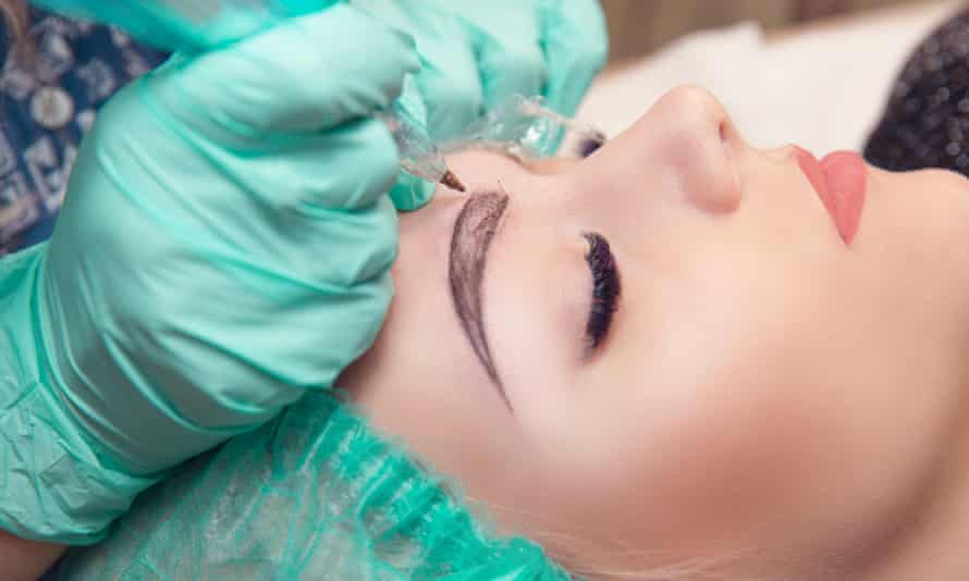 Gloved hands microblading eyebrows