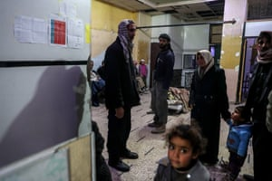 Injured people wait at a hospital in Douma