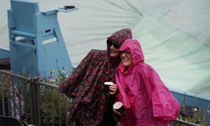 Spectators pose for a picture in front of a covered court as rain stops play during the Queens Club tennis tournament in London, Wednesday, June 19, 2019. (AP Photo/Kirsty Wigglesworth)
