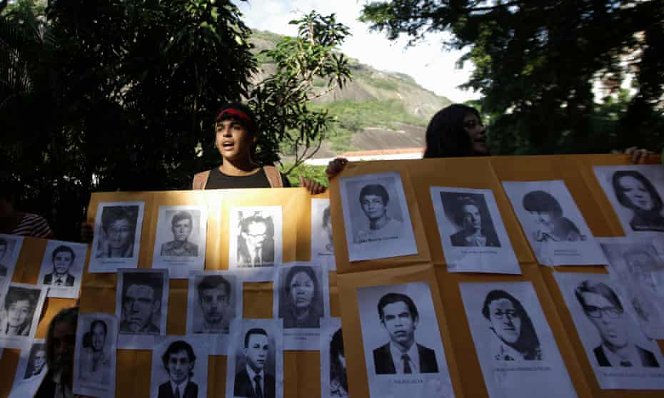 A man holds a placard with pictures of the victims of Brazil's military dictatorship at a 2012 protest in Rio de Janeiro.