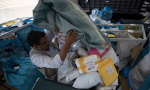 A Palestinian postal worker begins working through 10 tonnes of the mail at a sorting office in Jericho