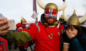 A Norwegian fan celebrates as Norway win gold and bronze in the women's 10km freestyle cross-country.