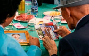 South Korean Choi Dong-Gyu (R, 84) and his North Korean family member Park Choon-Hwa (58) look at their family photos at a dinner.