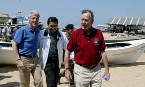 George HW Bush, right, walks with his fellow former president Bill Clinton and the Thai foreign minister in February 2005 as they survey damage from the Indian Ocean tsunami.