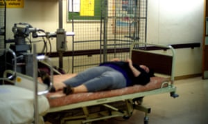 A patient lying forgotten in a hospital corridor.