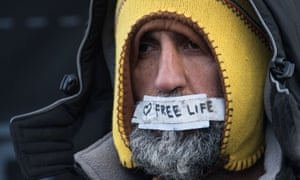A man with a note reading 'I love free life' on his mouth protests against the dismantling of part of the Calais camp.